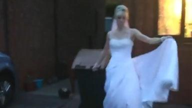 Woman wears wedding dress and takes out the trash.