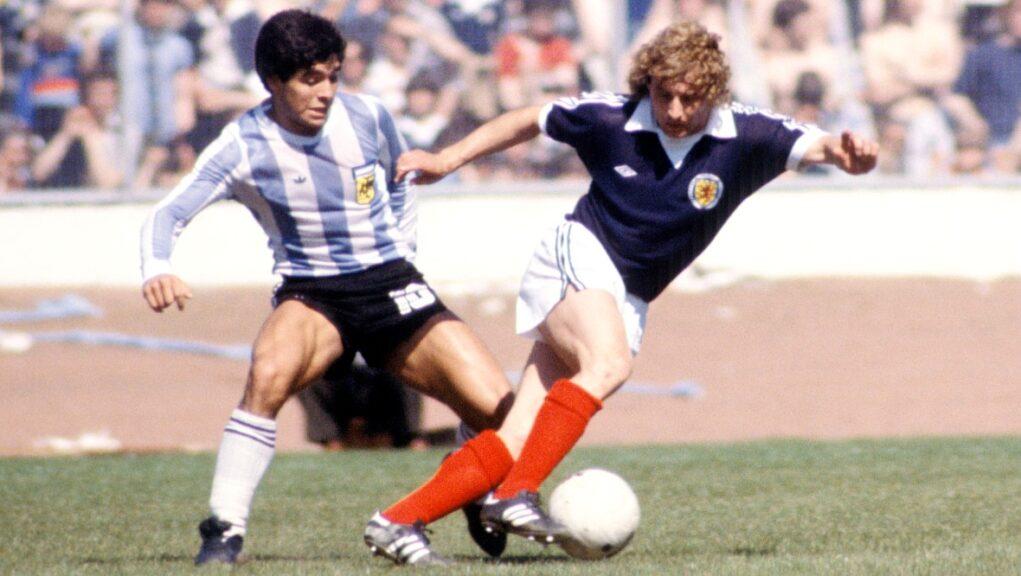 Maradona battles Asa Hartford for possession in front of a full house at Hampden.
