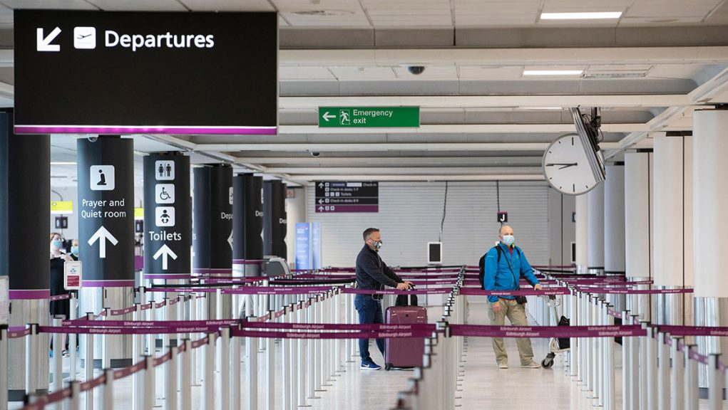 Passengers wearing protective face masks at the Edinburgh Airport check-in area.