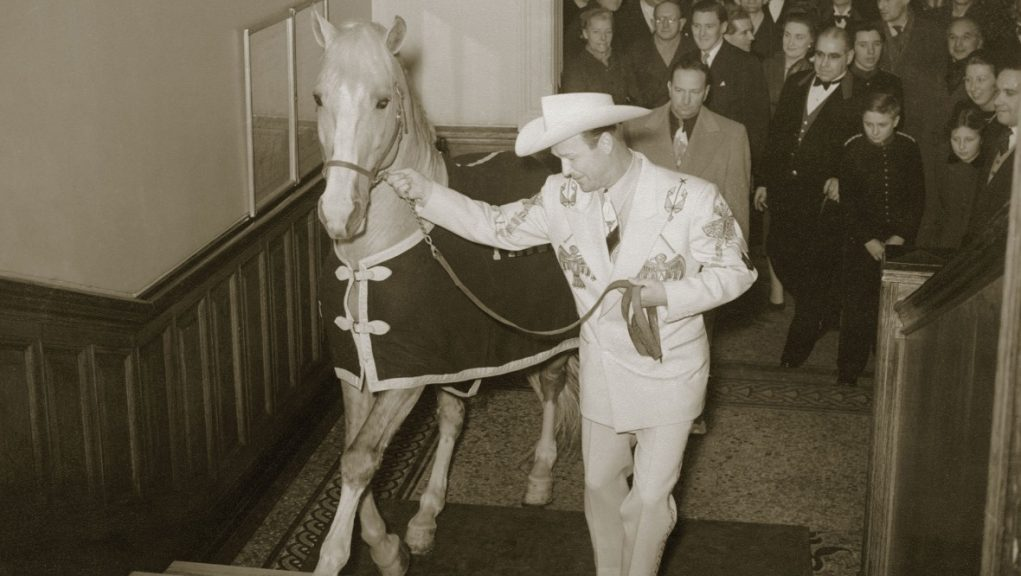 Western star Roy Rogers and his horse Trigger climb the hotel stairs.