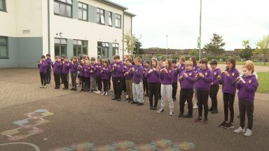 Primary school pupils learn to play woodwind instruments.