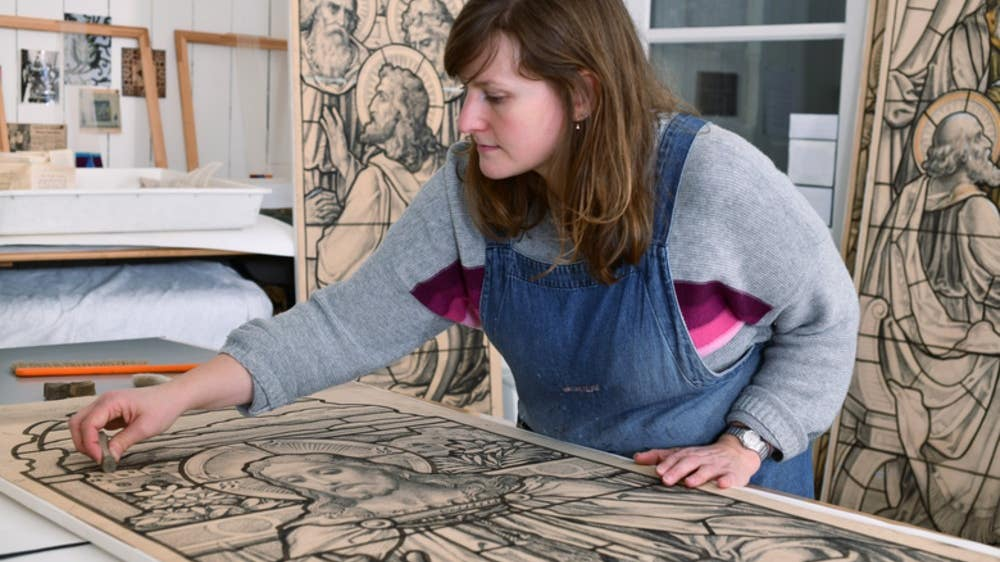 Conservator Anna Trist with one of the artist's panels.
