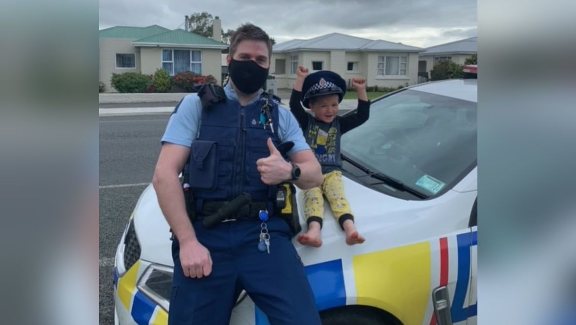 Constable Kurt with the boy sitting happily on the bonnet of his police car.