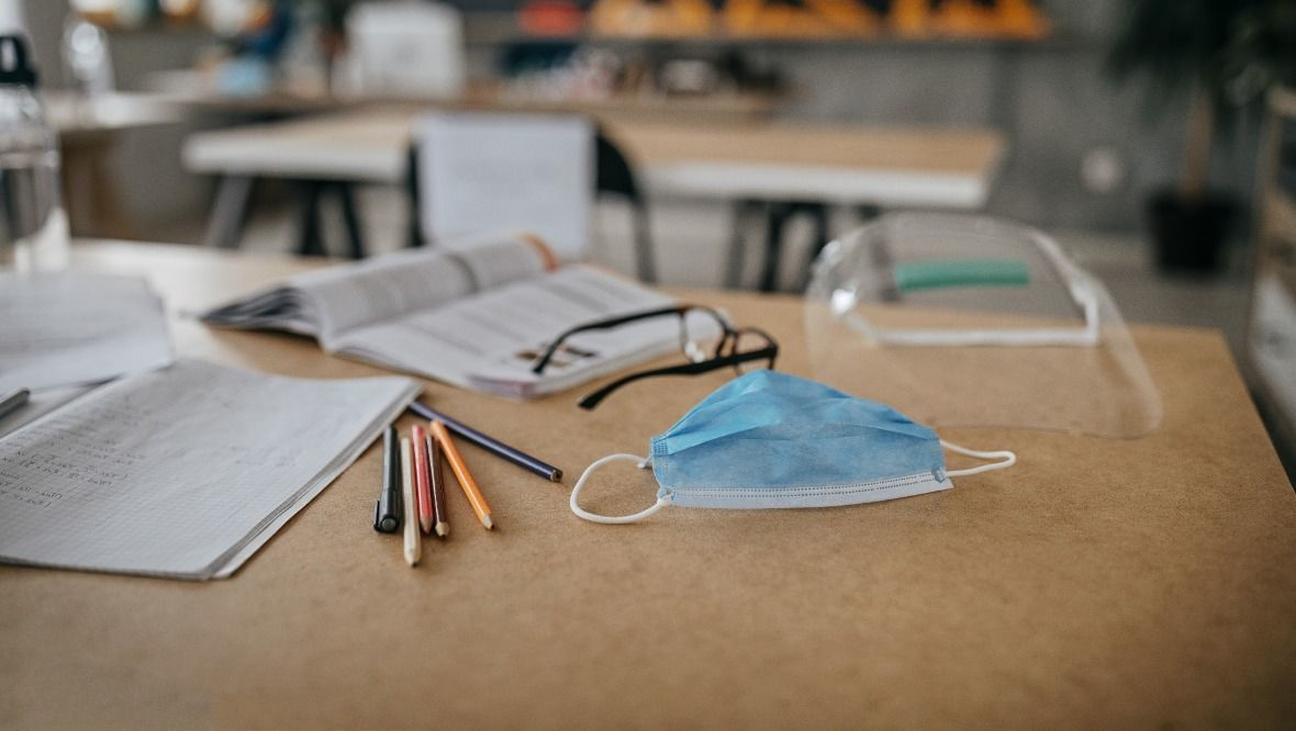 Stock image of face covering on school desk.