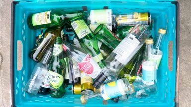 Stock image of glass bottles in recycling box.